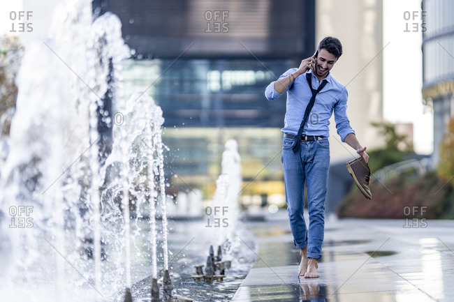 Smiling businessman talking on mobile phone holding shoe while walking barefoot by fountain