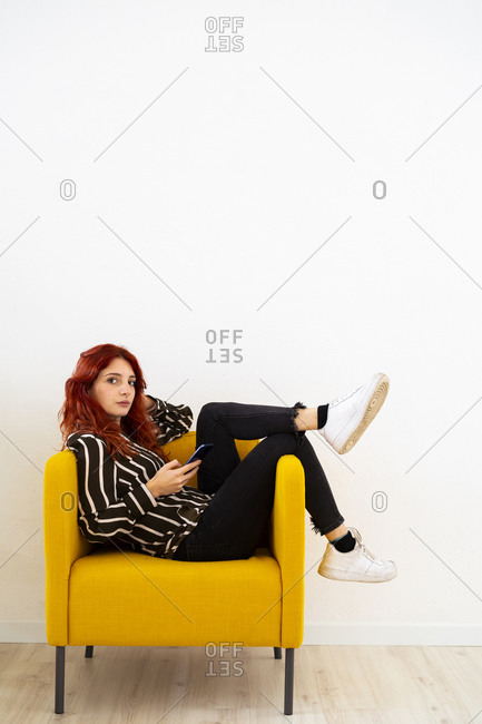 Redhead woman using mobile phone while resting on arm chair at office