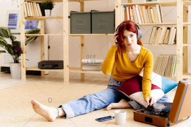 Redhead young wearing headphones using turntable while sitting at home