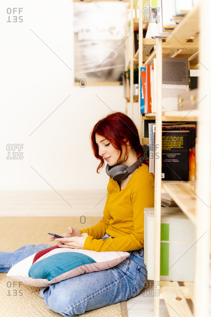 Young woman with headphones using mobile phone while sitting by bookshelf at home