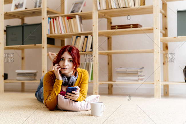 Woman with coffee cup using mobile phone while lying on carpet at home