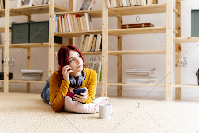 Thoughtful woman with mobile phone looking away while lying on carpet at home