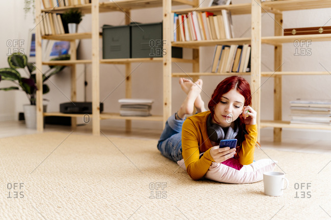 Young woman using mobile phone while lying on carpet at home