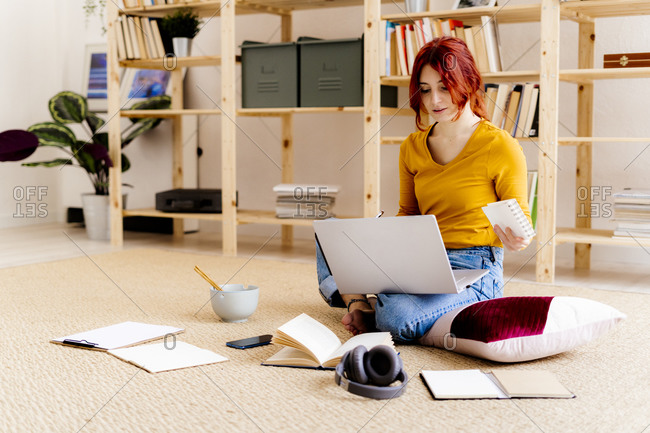 Young woman using laptop while sitting against bookshelf at home