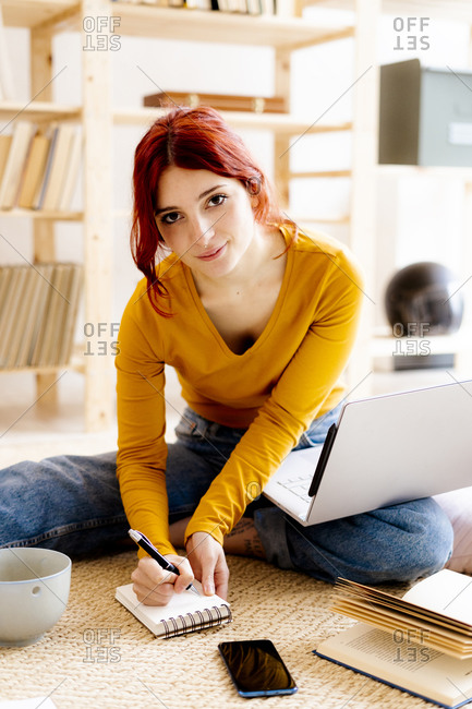 Young woman with laptop on lap writing in note pad while studying at home