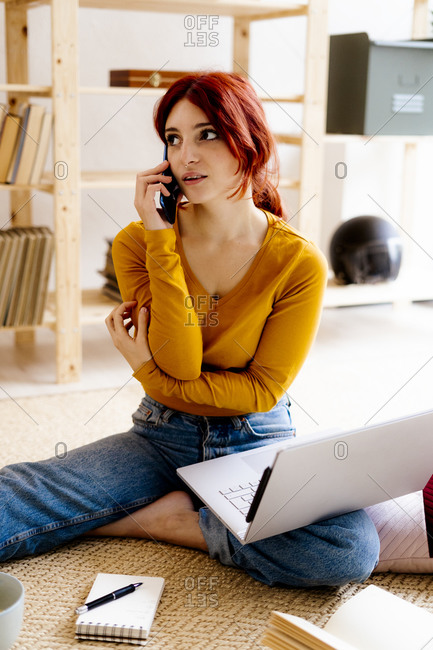 Young woman with laptop discussing on mobile phone while studying at home