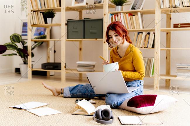 Smiling woman using laptop while having food sitting at home
