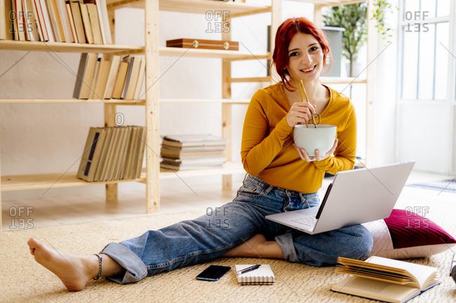 Smiling woman having food while studying through laptop sitting at home