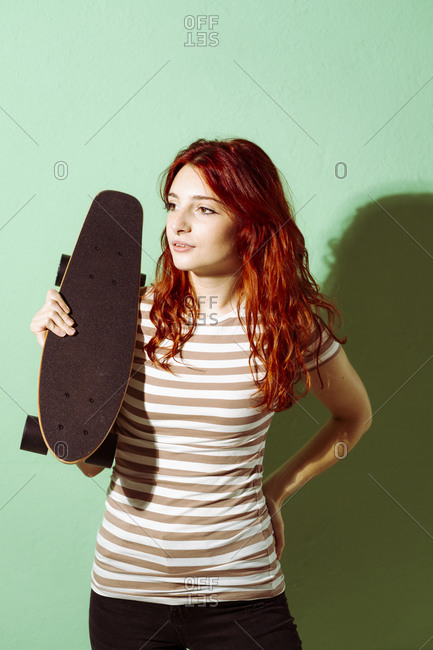 Young redhead woman holding skateboard while standing against green background
