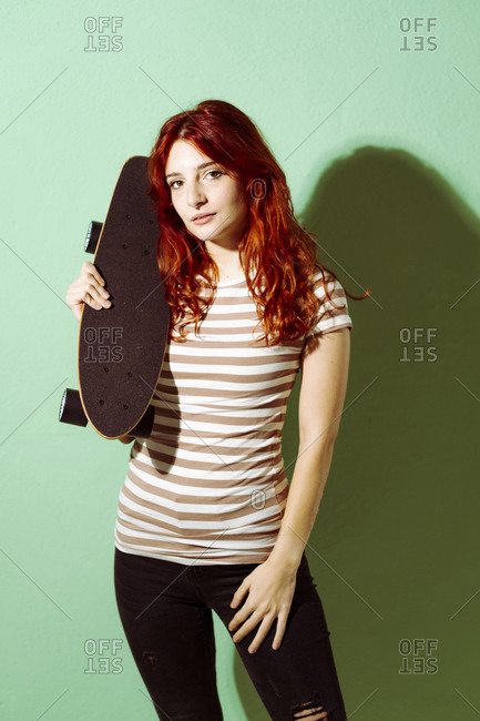 Redhead woman holding skateboard while standing against green background