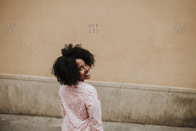Smiling woman looking over shoulder while standing by wall