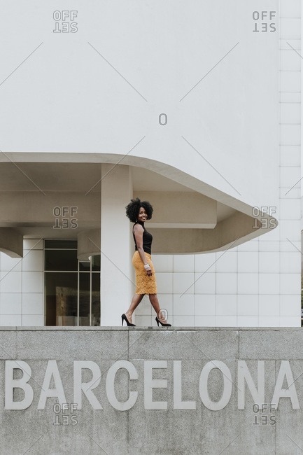 Mature woman walking on retaining wall with Barcelona text