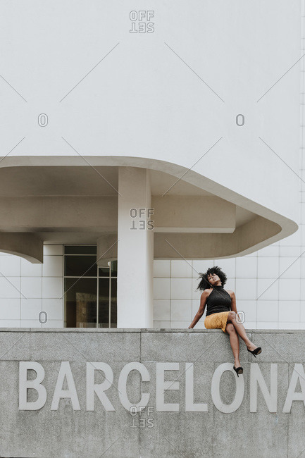 Carefree woman sitting on retaining wall with Barcelona text