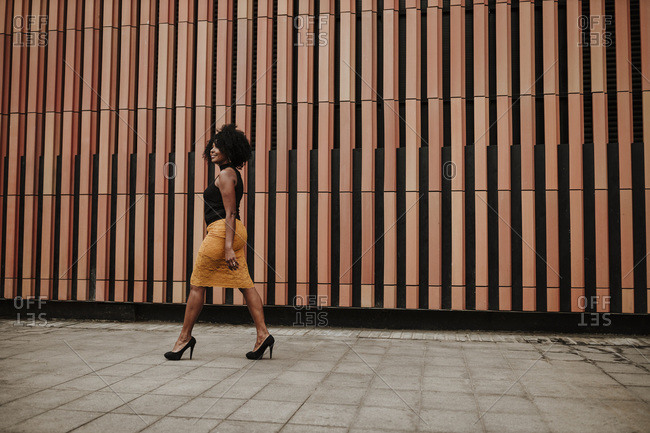 Mature woman walking on footpath by striped wall
