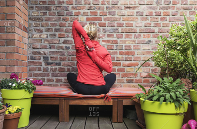 Mature woman stretching hands behind back while exercising in balcony