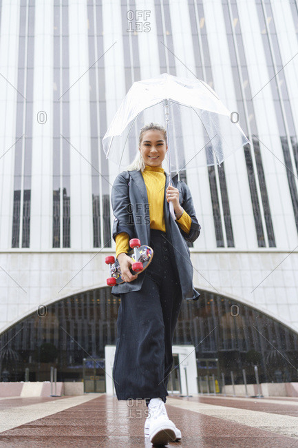 Happy businesswoman walking with umbrella while holding skateboard against building on rainy day