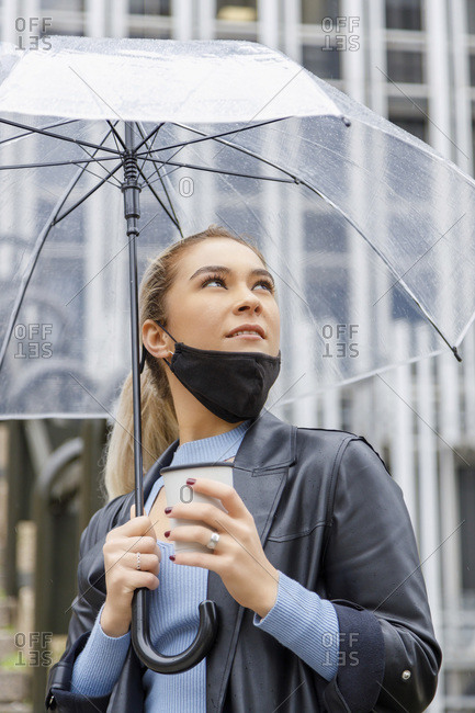 Thoughtful businesswoman wearing face mask holding umbrella and disposable cup in city during rainy season