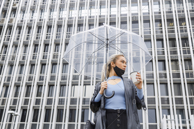 Female professional with umbrella holding disposable cup against building in city during COVID-19