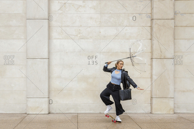 Young businesswoman holding damaged umbrella while skateboarding against wall on rainy day