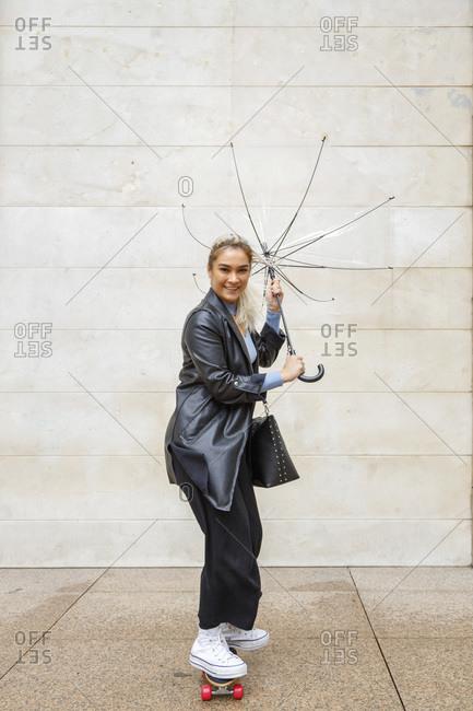 Smiling businesswoman on skateboard holding damaged umbrella against wall rainy day