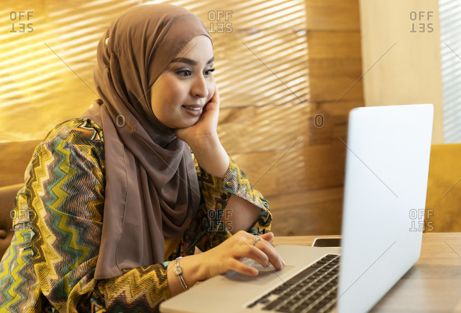 Young woman wearing hijab sitting with hand on chin while working on laptop at cafe