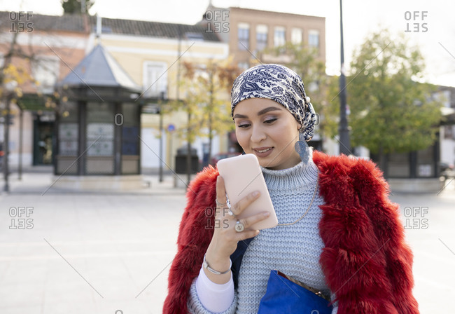 Young woman wearing warm clothing using mobile phone while standing in city