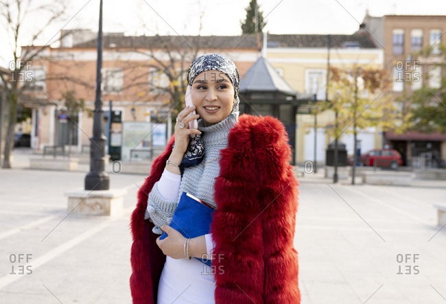 Young woman wearing fur coat talking on mobile phone while standing in city