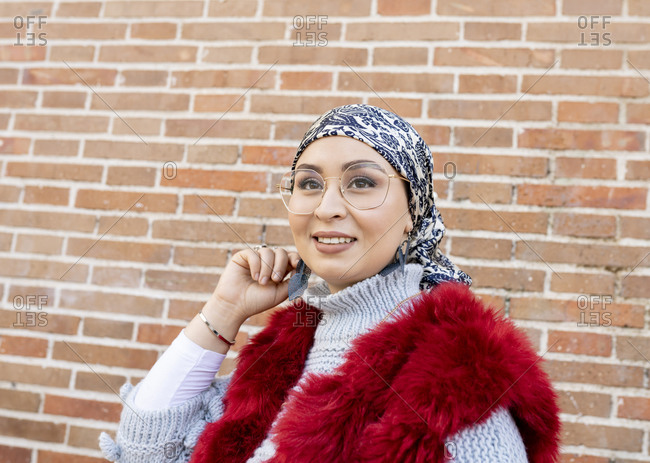 Woman wearing fur coat and eyeglasses looking away while standing against brick wall