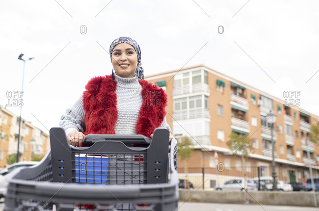Smiling woman standing with shopping cart at city