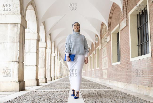 Young woman wearing headscarf walking at corridor