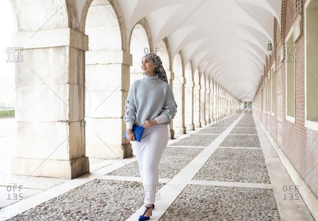 Smiling woman looking away while walking at corridor
