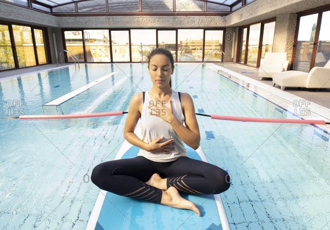 Female yoga instructor meditating on paddleboard over swimming pool