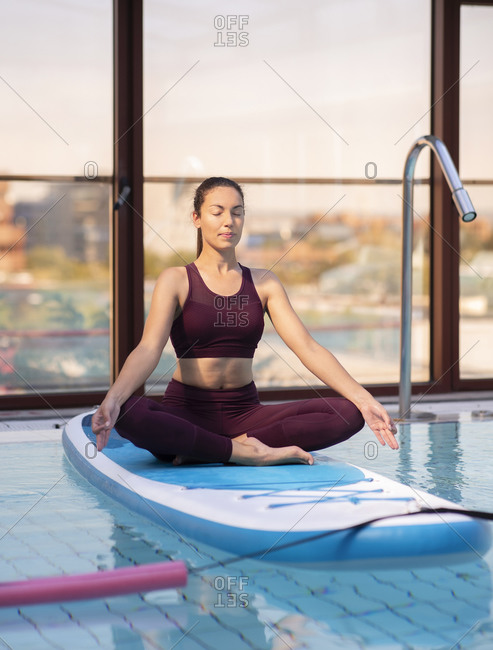 Mid adult female instructor meditating on paddleboard over swimming pool