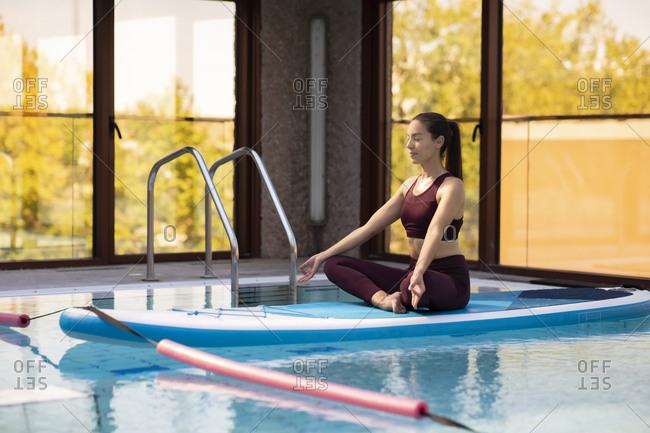 Female SUP yoga teacher meditating in lotus position over swimming pool