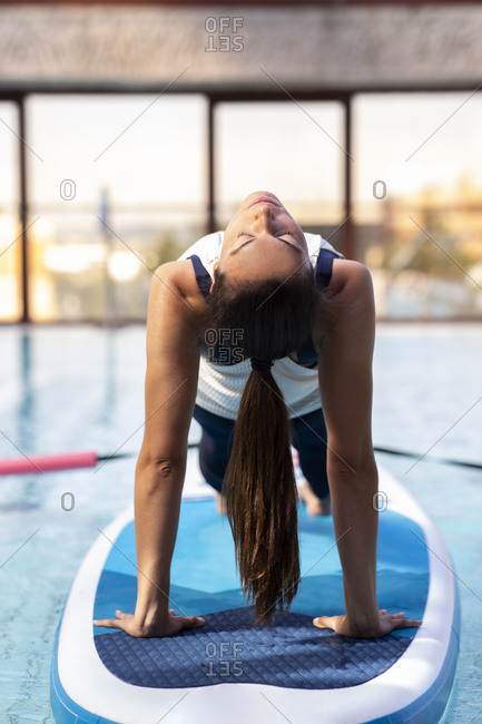Female yoga instructor in bridge position on paddleboard over swimming pool