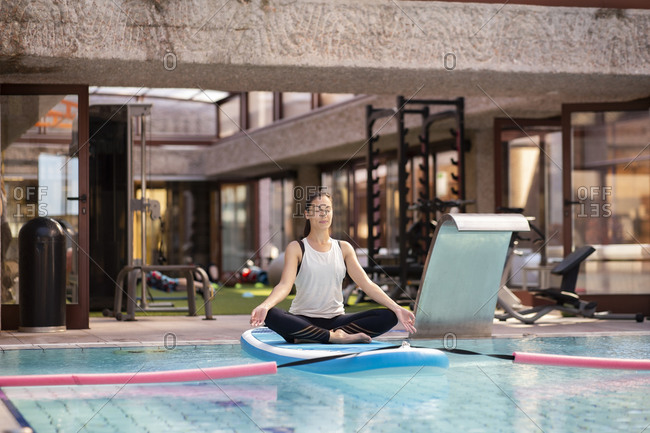 Female yoga teacher in lotus position on paddleboard over swimming pool
