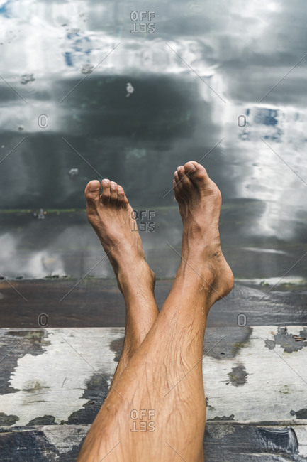 Bare feet of man relaxing on steps of underground cenote