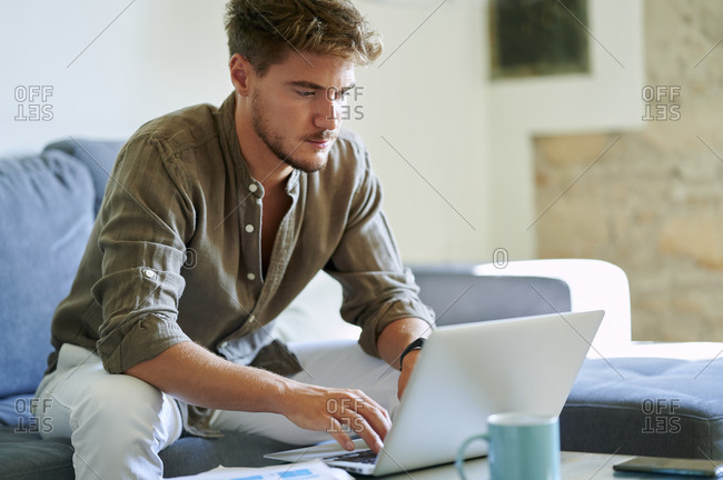 Male freelancer using laptop while working at home