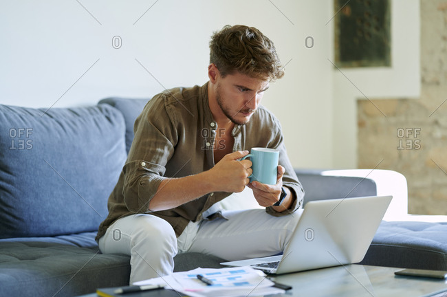 Young male entrepreneur holding coffee mug while working on laptop in living room