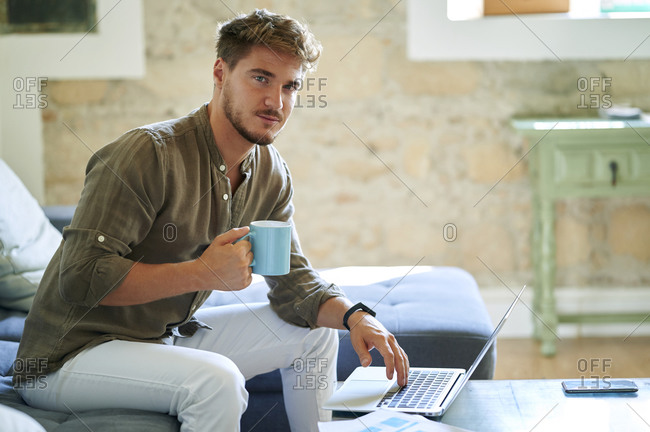 Male freelancer holding coffee mug while sitting by laptop at home
