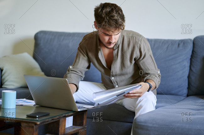 Young male freelancer reading documents while sitting on sofa with laptop at home