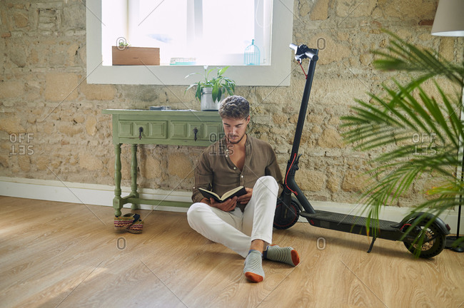 Young man reading book while sitting on floor by electric push scooter at home