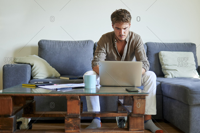 Businessman concentrating while working on laptop at home