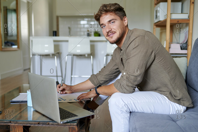 Smiling businessman sitting with documents at home