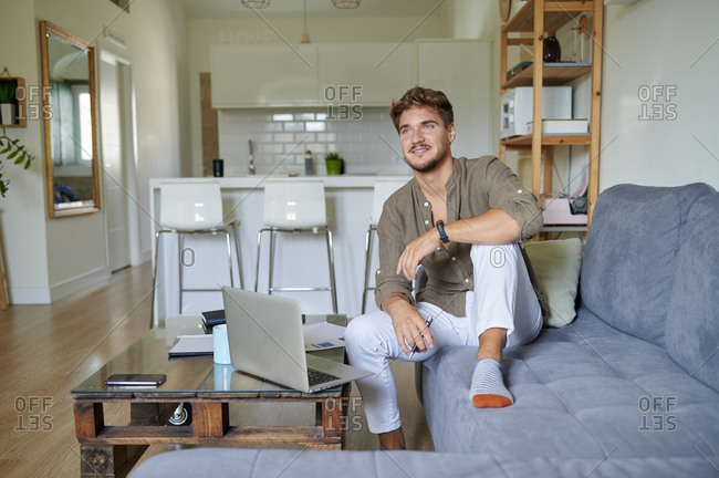 Thoughtful male freelancer looking away while sitting on sofa in living room
