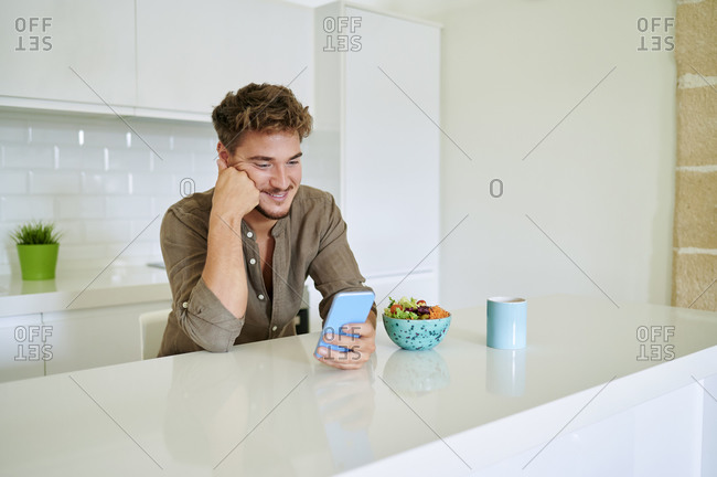 Smiling man using smart phone while leaning on kitchen counter at home