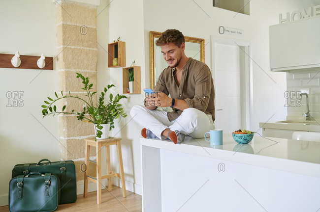 Smiling man text messaging on smart phone while sitting over counter in kitchen at home