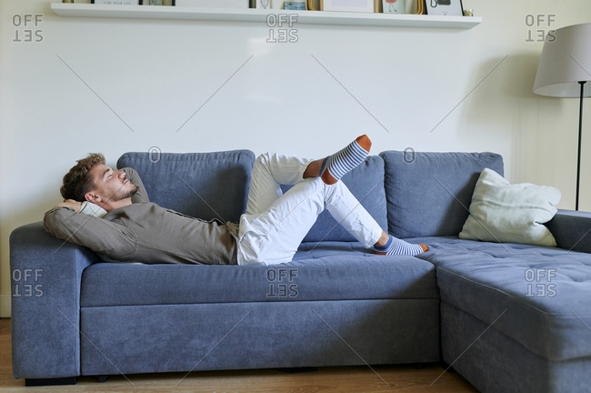 Man resting on sofa with hands behind head in living room at home