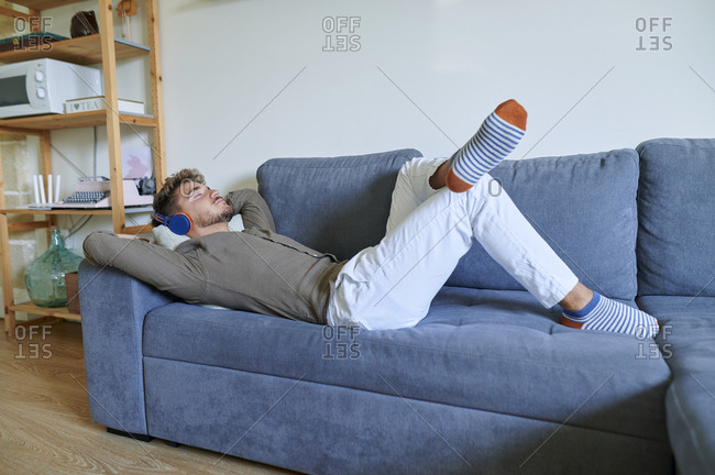 Young man with headphones listening music while lying on sofa at home