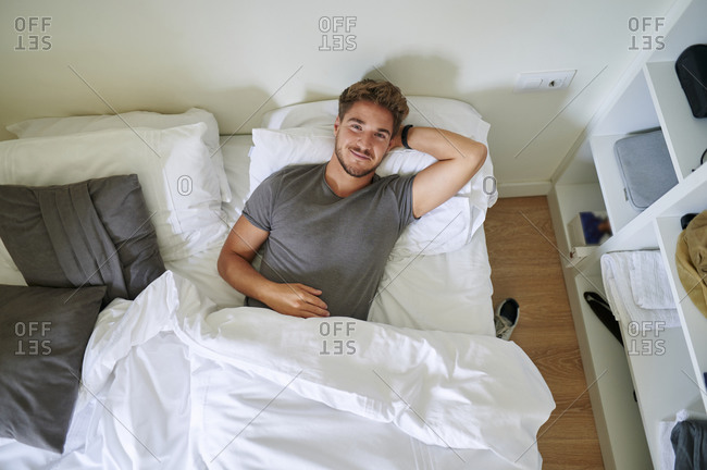 Smiling man with hand behind head resting in bedroom